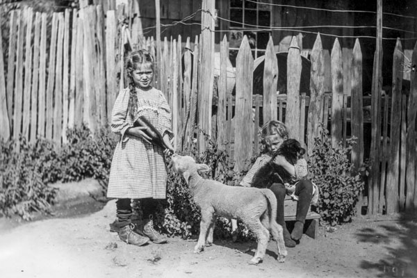 black and white photo of two children with a sheep and a dog