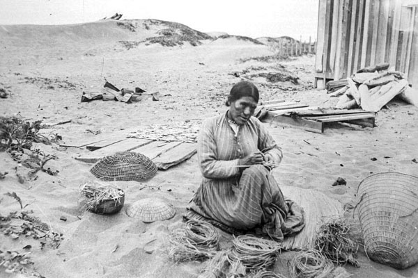 black and white photo of Sally Tom weaving a basket