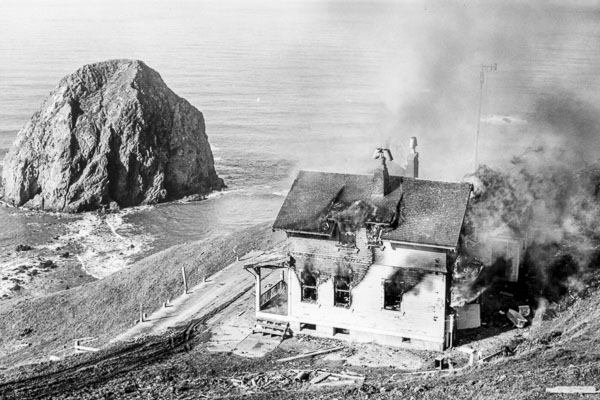 Photo of a burnt house next to the ocean