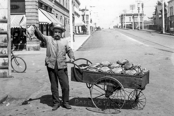 black and white photo of a man with a cart full of crabs