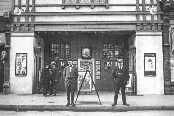 black and white photo of a man in a suit standing in front of a theater