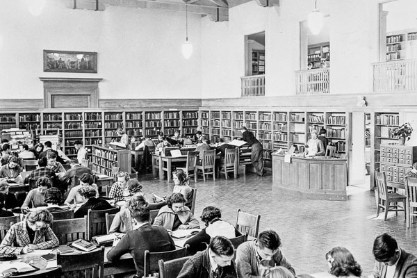 black and white photo of students in a library