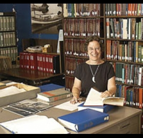 Joan Berman at a desk reviewing papers with bookshelves behind her