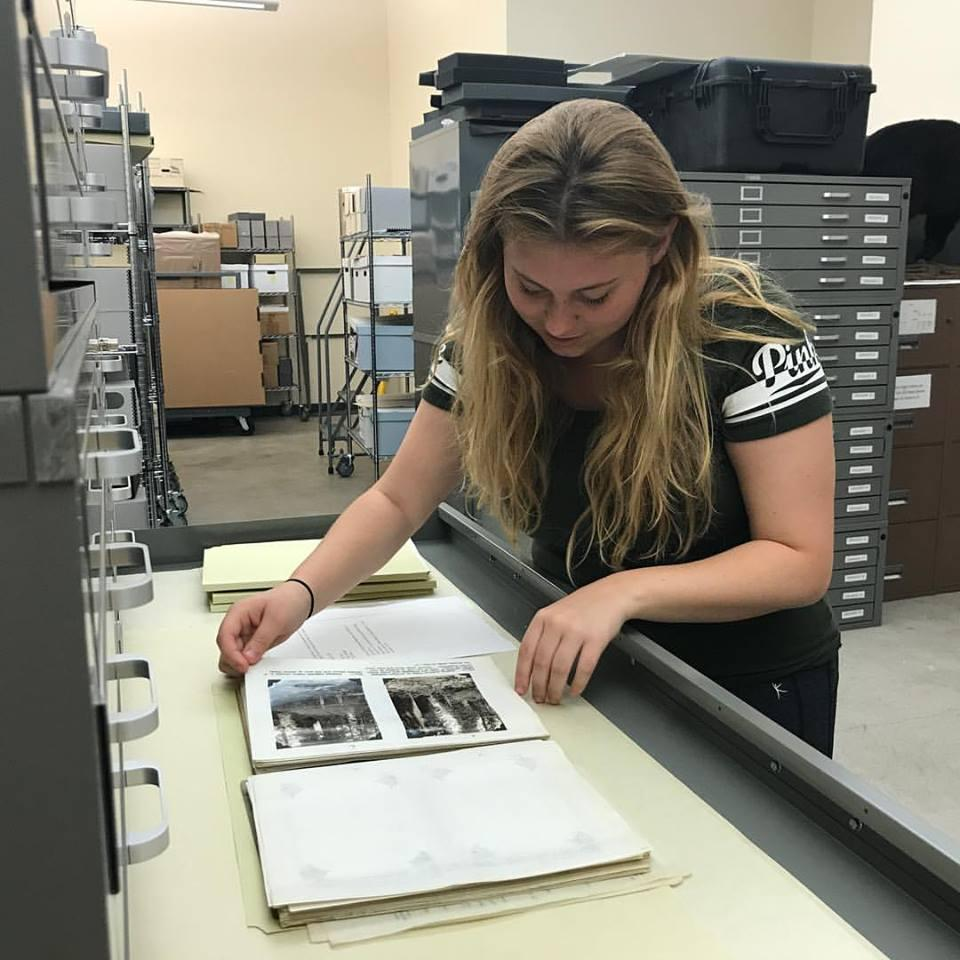 Intern views photos in a metal archival shelf