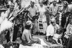 black and white image of Native American women and children surrounded by others in traditional dress