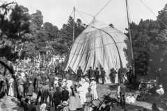 black and white photo with many people standing around a tent