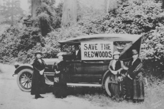 An old car with save the redwoods on it and women standing around it in dresses